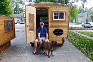 Peter Pavlowich sits in the doorway of the tenth Casual Turtle Camper he's hand built in his driveway in Fort Collins, Colorado.